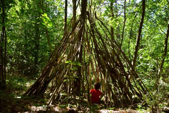 child sitting cabin forest