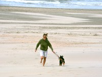 girl with sunglasses running with dog at the beach.jpg