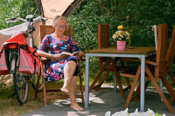 woman reading book campsite